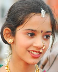 Pretty young lady is bedecked in Indian jewelry and shows a lovely smile.. Faces of India. Stunning...