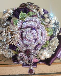 Jeweled wedding bouquet designed with, crystal brooches, pearls, amethyst hand rolled roses, purple and, plum ribbons.