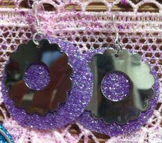 Orecchini creati da pendente fiore argento e base cerchio viola argento, ritagliata da una lastra ottenuta con colla e brillantini.