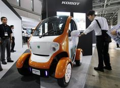 A visitor looks at a Kobot mini single-seater electric vehicle displayed at the Eco Office Expo in Tokyo on July 13, 2012