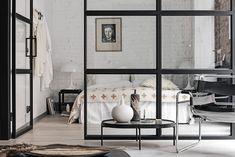 Alvhem. Ett loft där tegelväggarna varsamt knackats fram och där sovrummet avgränsas av en industriell glasvägg.