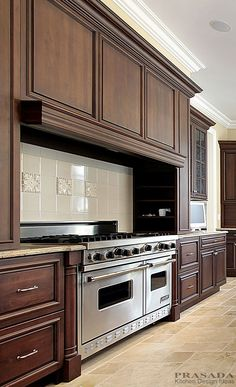 "Traditional Kitchen.  Dark stained cabinetry with large range hood and 48"" range.  www.prasadakitchens.com"
