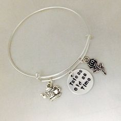 This Disney inspired bangle is made with a 3/4, 20 gauge nickel disc and stamped with Tale As Old As Time from the Beauty And The Beast movie and includes a rose and teapot metal charms. They are all hung on an expandable stainless steel bangle. Every piece is lovingly hand stamped by me one letter at a time to create a unique treasure for you. Because of that, it is impossible to guarantee that letters will be perfectly aligned. I believe this lends to the charm of each piece.  Each one…