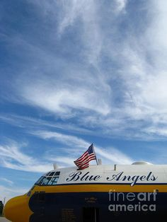 The American flag waves in a summer breeze over Fat Albert, the support C-130 for the Blue Angels in this color photograph by Bill Tomsa.