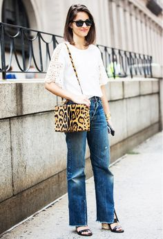 A white top with lace sleeves is paired with a pair of bootcut jeans, cork heels and a leopard box bag