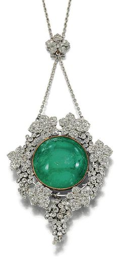 EMERALD AND DIAMOND PENDANT. The pendant designed as a central cabochon emerald within a surround of fruiting vines decorated to the front and back with millegrain-set circular- and rose-cut diamonds to a floral connecting link set with rose-cut stones, length approximately 380mm, fitted case Koch, Frankfurt A/M. B.Baden. c. 1905.