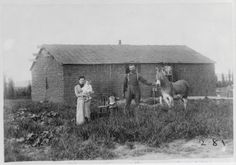 Black and white photograph of a white farming family standing with a mule in front of their home.