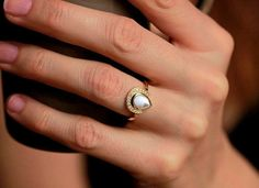 This showstopping engagement ring has a pear shaped pearl setting topped off with small diamonds.