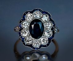 An Edwardian Era Sapphire and Diamond Engagement Ring  circa 1910   This finely crafted fancy cluster ring features an oval sapphire center in a millegrain platinum setting, framed by bright white and sparkling ten Old European cut round diamonds which, in turn, are outlined with a curvaceous border of tiny calibre-cut sapphires.