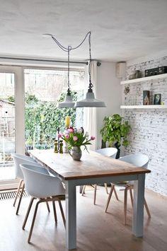 deux lampes pendantes industrielles, un mur en briques blanches, chaises modernes en bois et plastique