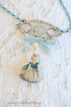 Hello Friends!Im happy to unveil the sweetest necklace I just finished making.This pale blue dreamy necklace was handmade with lots pretty bits and the shining star being the little vintage Marie Antoinette knit doll.She is a rare gem of a treasure! I found her two years ago at the…