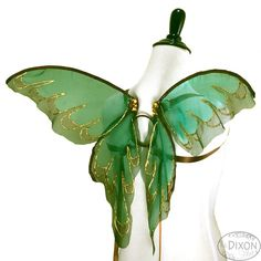 Light and airy fairy wings made with sheer green organza, airbrushed with brown paint along the edges, which have been sealed to prevent fraying, accented with golden sections and detailed with gold glitter. They are built on a newly designed frame that can be worn either with the straps or tucked into a close fitting bodice for a strapless look. These wings are also hinged for ease of movement and transportability. Wings are worn by satin ribbons that go around your shoulders and are held…
