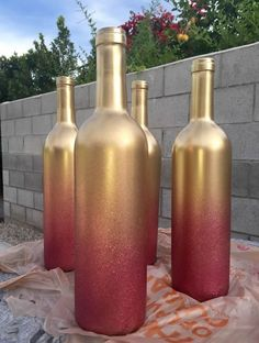 Step Get some wine bottles from a restaurant (or your own collection) Step Clean off labels Step Spray with metallic gold spray paint Step Spray 2 layers of pink glitter spray paint. Glass Bottle Crafts, Wine Bottle Art, Painted Wine Bottles, Diy Bottle, Glass Bottles, Glitter Wine Bottles, Painted Vases, Decorative Wine Bottles, Wedding Wine Bottles
