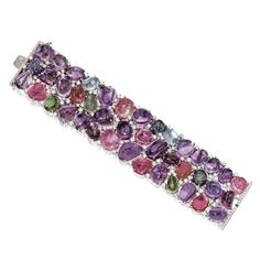 MULTI-COLORED STONE AND DIAMOND BRACELET The wide, articulated strap set with numerous cabochon multi-colored stones, studded with small round diamonds weighing a total of approximately 7.90 carats, mounted in 18 karat white gold, length 7 inches.