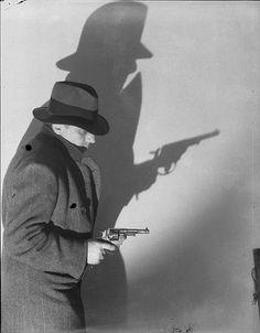 Roger Parry, Un homme en pardessus et borsalino, de profil, avec son ombre portée sur un mur, brandit un revolver, 1933-1934  Négatif noir et blanc, support pellicule Donation Roger Parry, Ministère de la culture (Médiathèque de l'architecture et du patrimoine) diffusion RMN