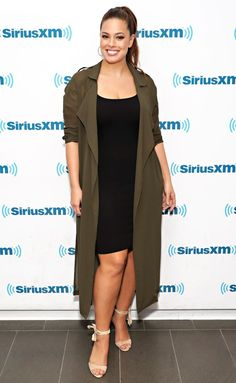 Ashley Graham in a black mini dress and green trench coat