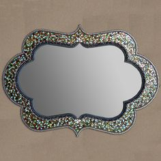 This intricately crafted mirror is handmade with hand-shaped Italian glass tiles, beads and metal. Inspired by the rhythm and symmetry of Moroccan art and architecture, the mirror's mosaic border and vibrant colors create a memorable piece for your wall. Give yourself the gift of a luxurious home.