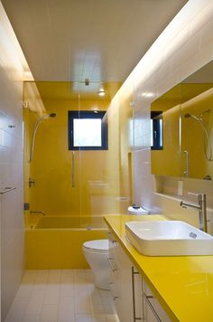 10 Inspirational Examples Of How To Include Yellow In Your Bathroom // The counter matches the bath/shower surround in this bathroom.