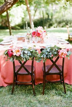 """Make a statement with your """"Mr. and Mrs."""" chairs by adding bright peonies and lush eucalyptus garlands."""