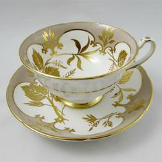 Royal Grafton tea cup and saucer set is grey with large gold leaves. The pattern is called Studio Leaf. There is gold trimming on cup and saucer edges. Markings read: Royal Grafton Fine Bone China Made In England Studio Leaf