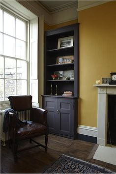 Lounge with walls in India Yellow Casein Distemper, shelving unit in Mahogany Dead Flat and trim in Old White Dead Flat.: