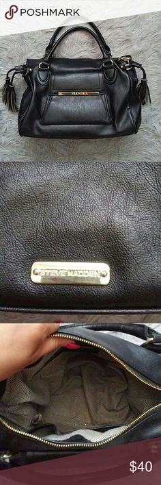 """Sale! Vegan leather tassel satchel Size: 14"""" across bottom Color: black and gold hardware Condition: good No holes Slight markings inside Non Smoking home Pet free home Style Tags: steve madden,   Fyi: if anything has obvious or noticeable stain, holes,discoloration, piling, etc it will be noted in the listing. Please be patient with questions as we all live in different time zones etc. I do trade. I do not provide any of my personal contact info. I will sometimes model my clothing. I've…"""