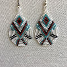 Native American Style brick stitch beaded teardrop fringe earrings Native American Style teardrop fringe beaded earrings made with size 13 Charlottes in white, red, black, and turquoise. Bead Jewellery, Seed Bead Jewelry, Seed Bead Earrings, Fringe Earrings, Boho Earrings, Beaded Earrings Patterns, Beading Patterns Free, Seed Bead Patterns, Native American Beading