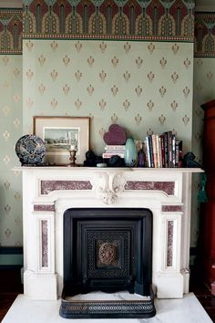 """The master bedroom's marble fireplace is highlighted with soothing green """"Roland"""" fill paper and a """"Victory"""" frieze from Bradbury & Bradbury. #bradburywallpaper"""