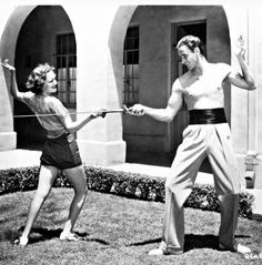 Olivia De Havilland and Errol Flynn practising swordfighting, c. 1930's.