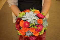 Rich and vibrant. Hot pink beauty aster, orange spray roses, green hypericum berry and succulents.