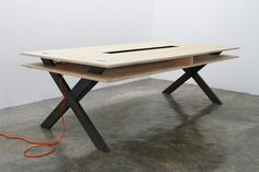 The Work Table 002 by Miguel de la Garza features a standard-size pine plywood surface of 6 ft. by 8 ft. that allows up to 6 people working at the same time with 8 sockets in the center of the table, as well as a second surface for storage.