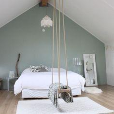 Une grande chambre sous une charpente peinte en blanc, un mur vert amande, du parquet et une balançoire. Calme, détente et un peu de folie.
