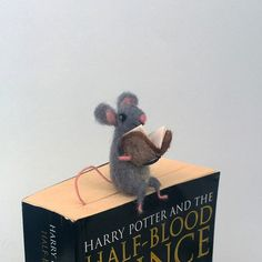 Mouse bookmark. Tiny mouse reading a book. His long tail is trapped in the book, but does not care because is reading very interesting book. His book