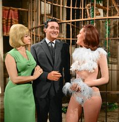 """A color still from """"The Girl from Auntie,"""" featuring Liz Fraser as a well-endowed version of """"Mrs. Emma Peel"""" alongside our usual Steed and Peel."""