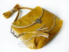 """sac """"nuage"""" en cuir jaune curry et passe poil doré et pomponSac en cuir """"nuage"""" réalisé dans un cuir grainé fin de couleur jaune curry.Il se compose d'une poche principale, une poche sur le devant en forme de nuage et une poche zippée au dos du sac et d'un rabbat avec un fermoir écolier en métal couleur bronze antique. Il peut se porter à l'épaule ou en bandoulière. La anse en cuir est ajustable grace aux mousquetons en métal et a la chaine en m�..."""