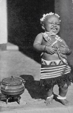 Child laughing next to a three leg cooking pot. South Africa. -  Scanned old postcard. ca. 1940's. °