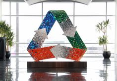 Iconic recycling symbol sculpture made with 6,000 reclaimed bottle caps for Logan Airport