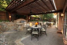 Entertain friends in this lovely kitchen and dining area under the inviting shade of the arbor. By Outdoor Signature in Argyle, TX