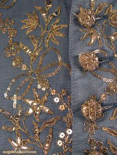 Detail from EMBROIDERED SLEEVED WAISTCOAT, 18th C. Slate blue horizontally ribbed silk embroidered in metallic gold, shaped gold paillettes & sequins, 20 CF buttons & 3 under each pocket, blue calmanco back & sleeves, blue silk cuffs, ivory silk lining