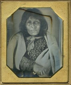 Sixth plate daguerreotype of an unidentified Native American woman, possibly from the Canadian Woodland Tribe. She is seated with a blanket around her shoulders and is holding an unidentified object in one of her hands.