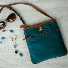 Michael Kors teal cross body purse ☆☆HP☆☆ Host pick 4/2. Teal nylon with brown trim. Adjustable cross body strap. Front exterior zip pocket, back exterior snap pocket, 2 interior pouch pockets.   No trades or PP.  Save even more with a bundle discount! MICHAEL Michael Kors Bags Crossbody Bags