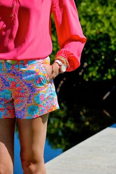 Bright pink and floral shorts with gold accents. Perfect combo against a summer tan.