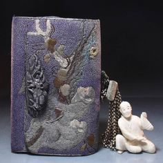 A Japanese Embroidered Tobacco Pouch Decorated with monkeys sitting in a leafy tree against a purple ground, with decorative white metal mounts and closure, a figural netsuke suspended by multiple chains. {Width: 5 1/2 inches (14 cm).