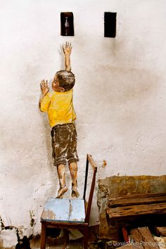 """Reaching Up is a mural painted on a wall along Cannon Street, George Town.     """"Reaching Up"""" depicts a little boy reaching for a hole (with a bottled drink) in the wall. He appears to be standing on a chair and inching himself as high as he could reach. The painting was created by Ernest Zacharevic in conjunction with the 2012 George Town Festival. Since its completion, increasing number of visitors had gone to take photos with it.    Copyright DonaldChen Photography"""