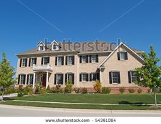 Huge two story brick home with black shutters.