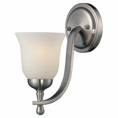 """Perfect in the dining room or master suite, this timeless wall sconce showcases a curving silhouette and fluted opal glass shade.    Product: SconceConstruction Material: Metal and glassColor: Brushed nickelAccommodates: (1) 60 Watt medium base bulb - not includedDimensions: 11"""" H x 5"""" W x 9"""" D"""