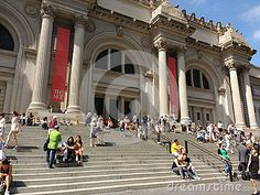 The main entrance of the Metropolitan Museum of Art, colloquially known as the Met. Located on 5th Avenue in Manhattan, New York City, the Met is the largest art museum in the United States of America. It`s a gorgeous, sunny day in the city. Some visitors climb the steps towards the front door while others sit on the stairs, enjoying the beautiful afternoon.