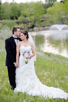 Intimate photo of bride and groom at nearby park in loving pose against pond with fountain Wedding at Baldoria on the Water in Colorado Joe loves Sterling Photos by Katie Corinne Photography
