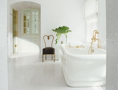This all-white maser bath is romantic and simple. Designer Sally Henderson chose surfaces that would give off a shimmery luster. The walls are a reflective milk glass, and the floors are glass mosaic. The gold fixtures are by Waterworks.