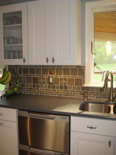 White cabinets, dark countertops and slate backsplash